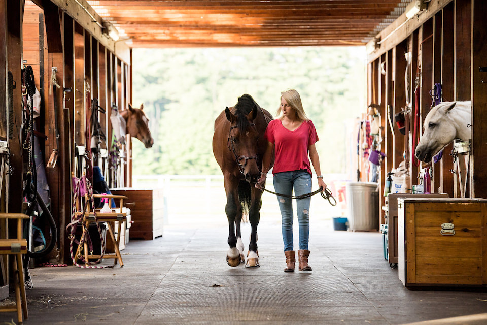 Young girl leads her horse through a barn