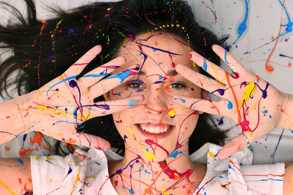 Girl covered in colored paint for senior portrait