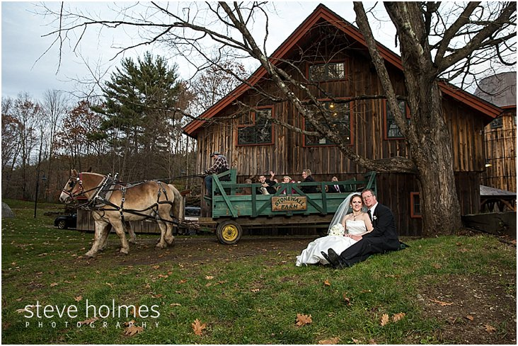 32_bride-groom-sit-on-ground-while-wedding-party-is-in-horse-drawn-cart-in-front-of-barn