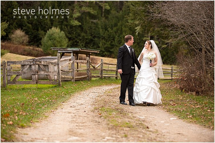 34_bride-groom-hold-hands-while-walking-down-gravel-road