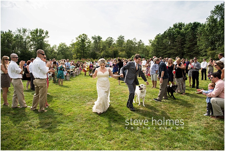 43_bride-and-groom-holding-hands-as-they-walk-down-aisle-after-ceremony