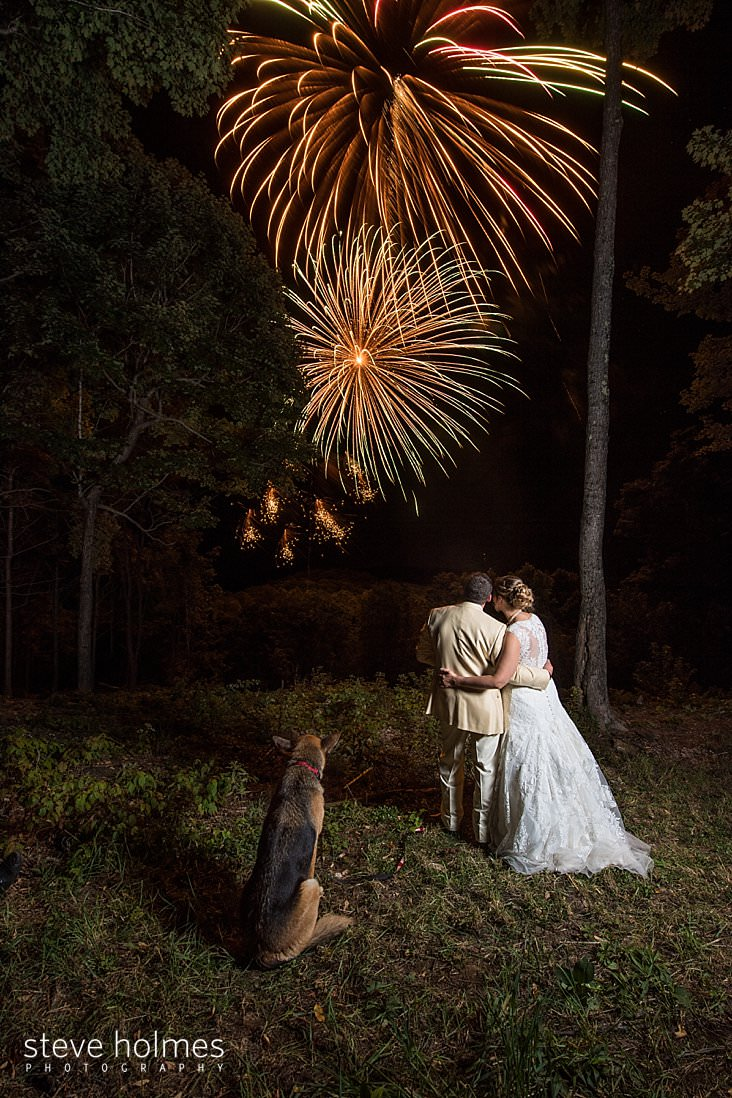 Bride, groom and dog watch fireworks