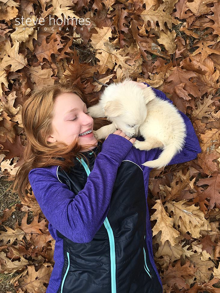 Young girl plays with a puppy in the leaves