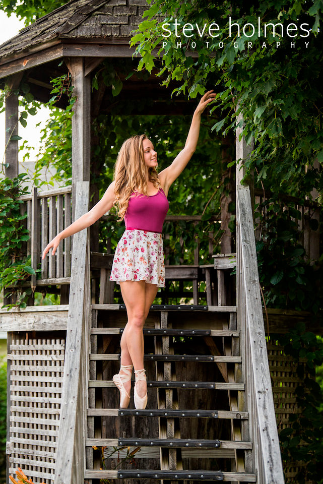 teen girl poses in her ballet shoes on stairs to pergola