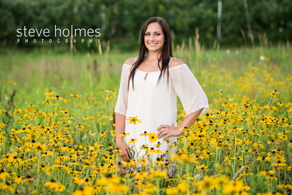 Teen girl stands in field of wildflowers