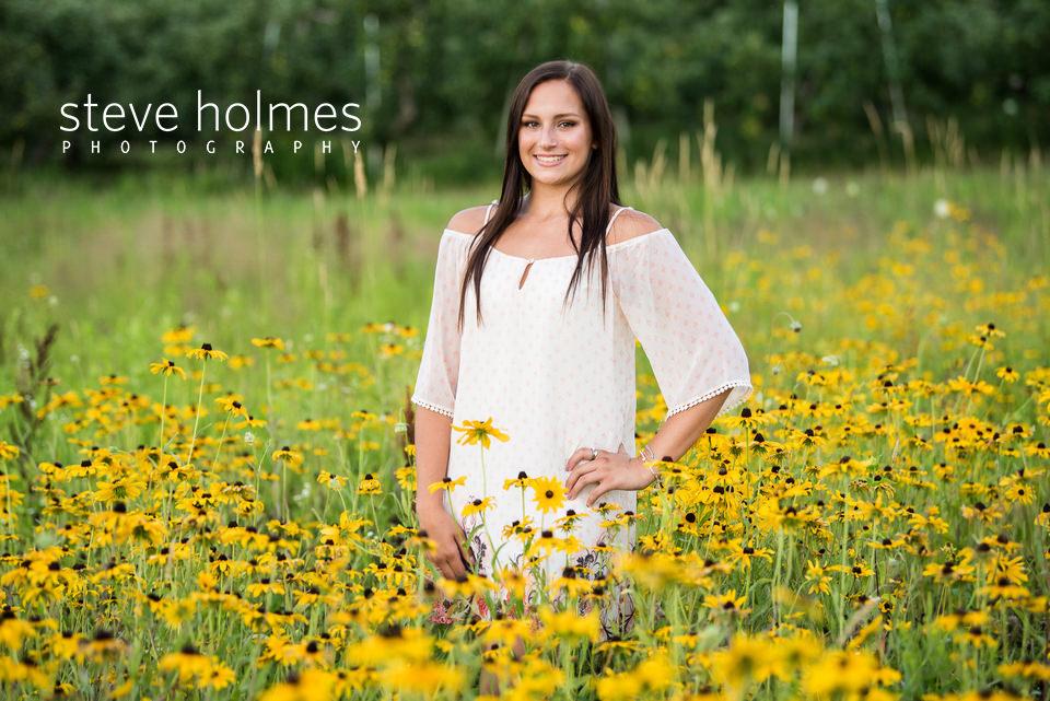 Teen girl stands in field of wildflowers