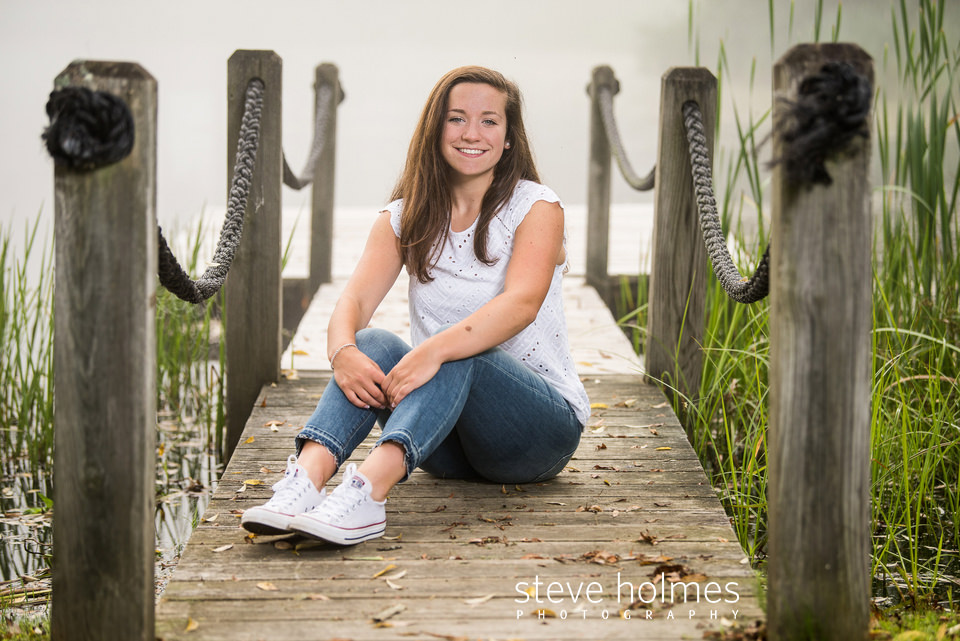 Young woman sits on dock in fog for senior portrait