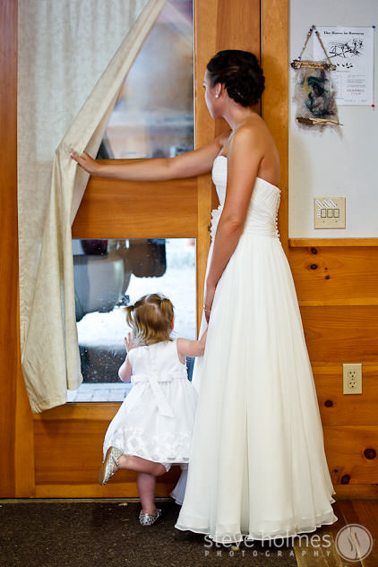 Bride and baby daughter look out the window while getting ready