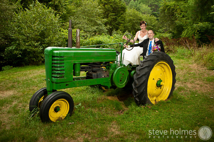 Bride and Groom pose for portrait next to tractor