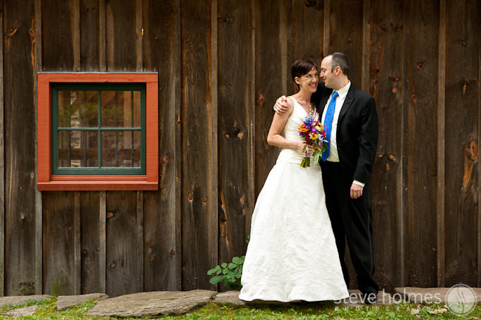 Bride and Groom pose next to wooden barn with red window