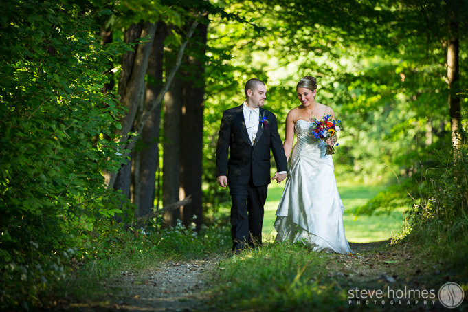 Bride and Groom walk down summer path together