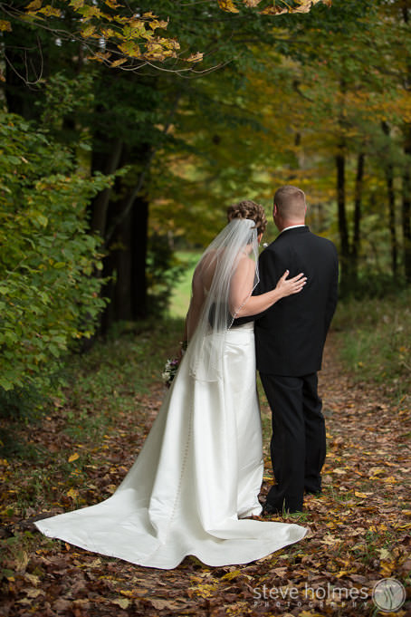 Bride and groom look down autumn country road