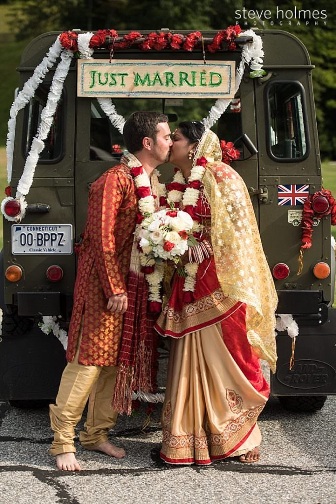 "Bride and groom in traditional Indian attire kiss in front of land rover decorated in red and white flowers and ""Just Married"" sign"