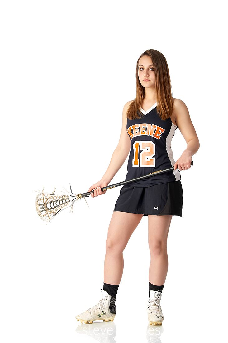 03_Young woman poses wearing field hockey gear in studio senior portrait.jpg