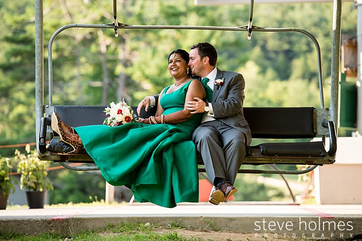 Groom whispers to bride as they sit together on chairlift