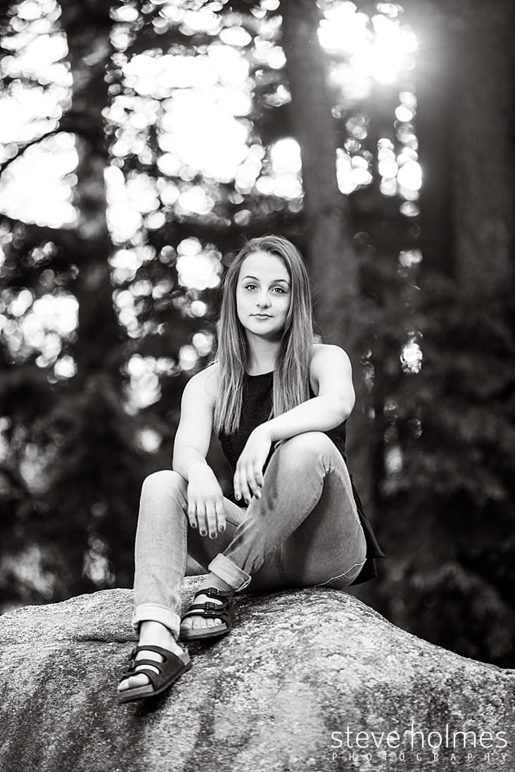 14_Black and white portrait of a teen girl in jeans sitting on a rock outside.jpg