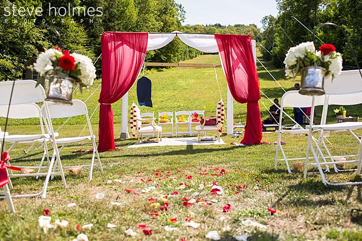 Wedding altar with flowing red curtains and chairs facing each other is prepared for ceremony