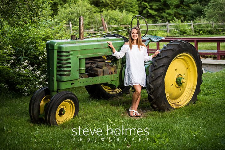 26_Teen in white dress and sandles poses for senior portrait next to a tractor.jpg