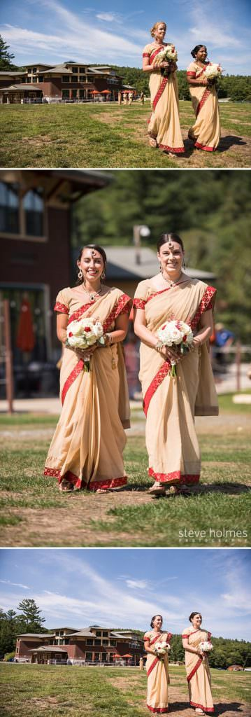 Bridesmaids in red and gold saris walk down isle