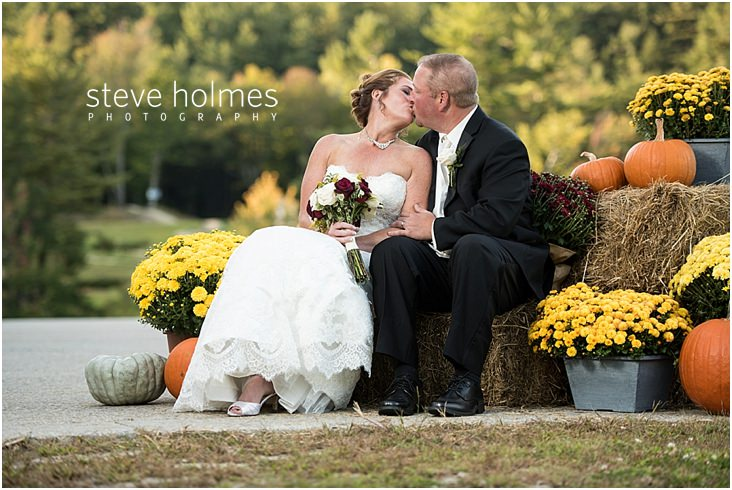 Bride and groom kiss amongst fall wedding decor