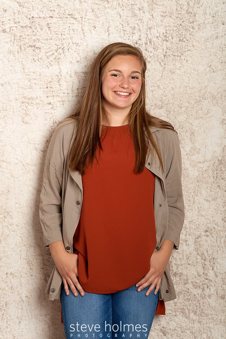 01_Young woman poses for studio senior portrait wearing jeans, orange blouse and tan long sleeve shirt.jpg