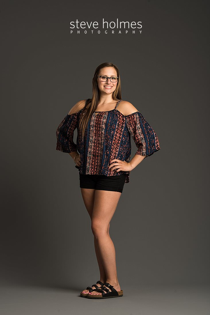02_Brunette teen wearing patterned blouse and black shorts poses with hands on her hips for studio portrait.jpg