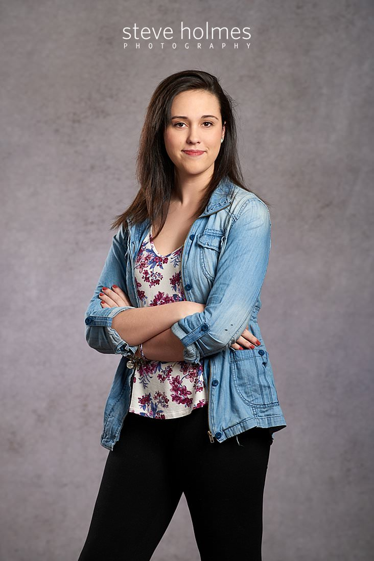 02_Studio portrait of brunette young woman standing with her arms crossed wearing jean jacket and floral shirt.jpg