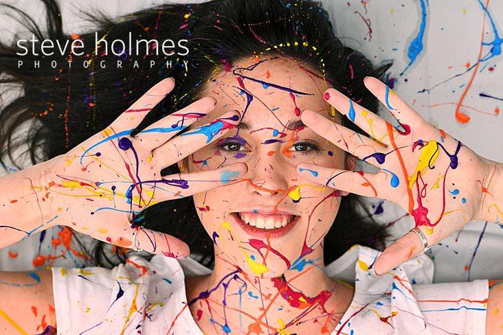03_Brunette teen is splattered in colored paint for studio senior portrait.jpg