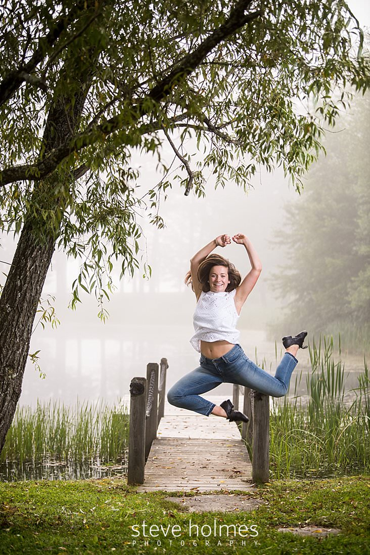 04_Teen girl leaps into air wearing jeans and white blouse next to foggy pond for senior photo.jpg