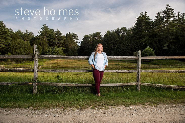 05_Blonde teen laughs with her hands in her jean pockets while leaning against fence.jpg