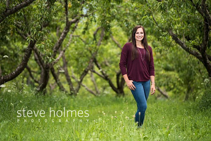 05_Brunette teen wearing maroon long sleeve and jeans poses in orchard for senior portrait.jpg