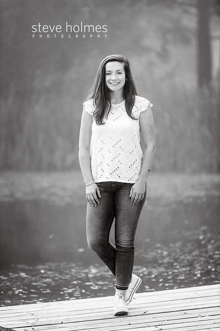06_Black and white outdoor senior portrait of teen girl standing on a dock of a foggy pond.jpg