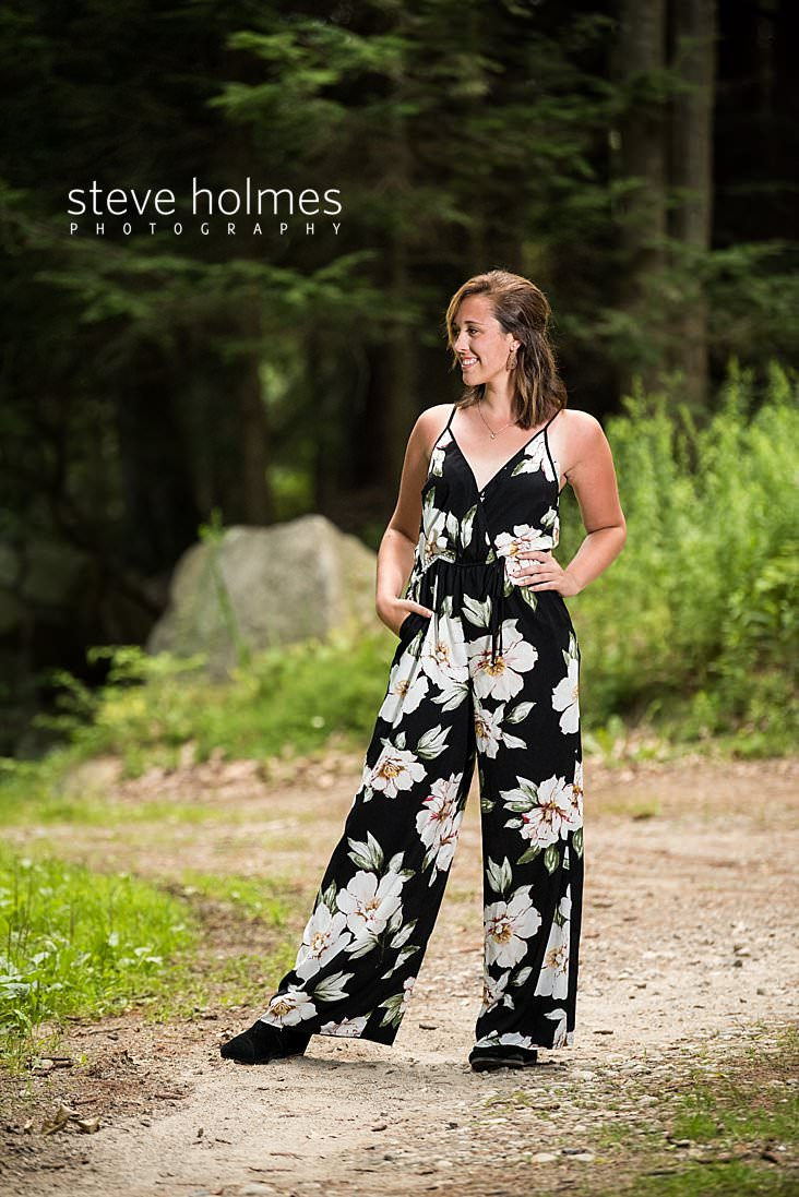 06_Teen girl in floral jumper poses for senior portrait on country road.jpg