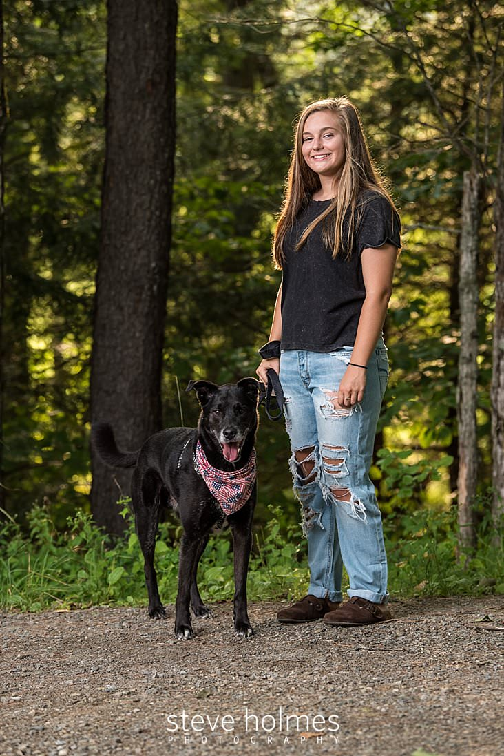 06_Teen girl with ripped jeans and black tee shirt stands with her dog on country road for senior portrait.jpg