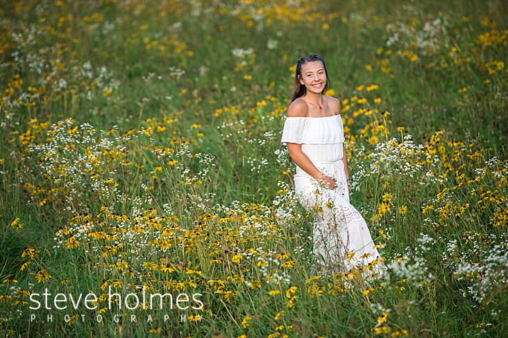 06_Teen wearing white dress walks smiling though field of wildflowers.jpg