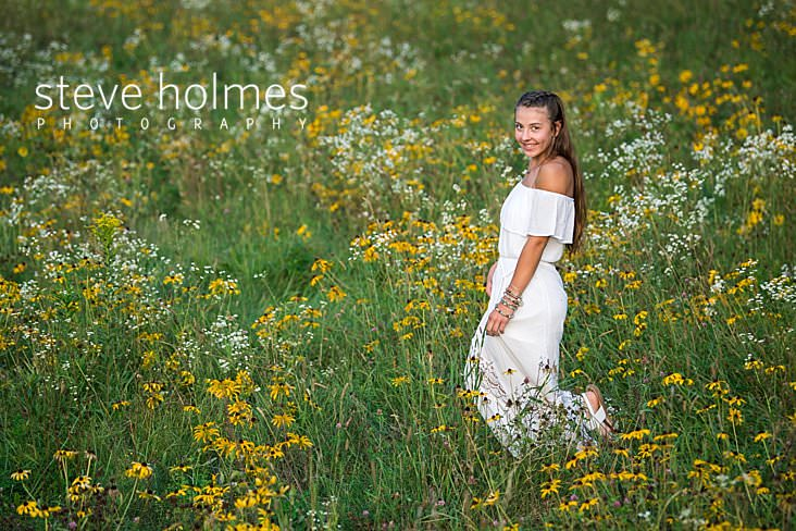 07_Smiling young woman looks at the camera while walking through field of wildflowers for senior portrait.jpg
