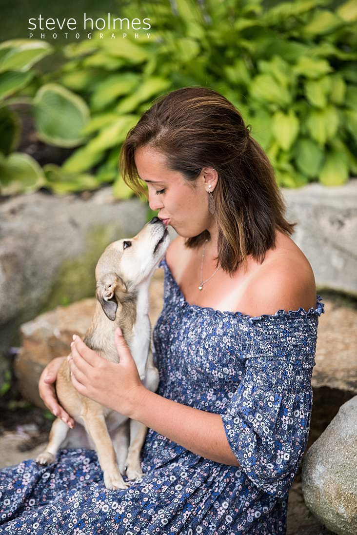 07_Teen girl in blue floral dress sits on a stone wall and gives her dog a kiss for senior photo.jpg