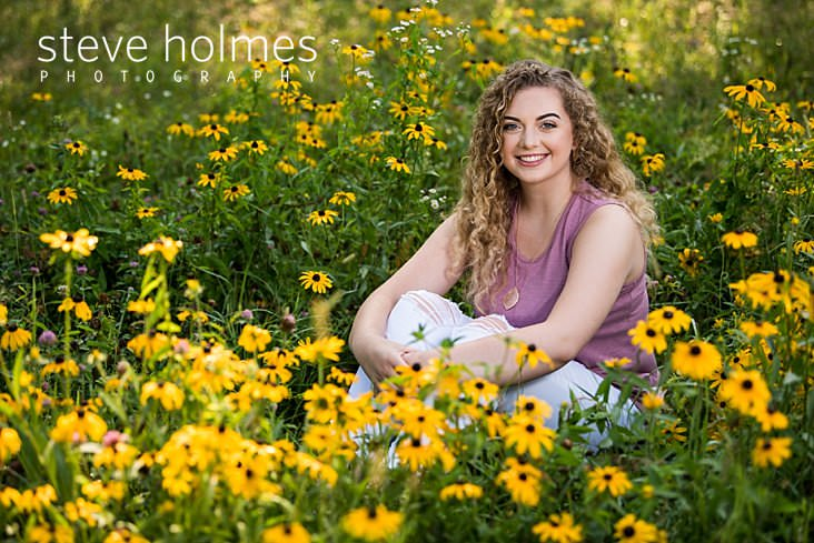 08_Blonde, young woman wearing white jeans and pink shirt sits in a field of wildflowers for senior portrait.jpg