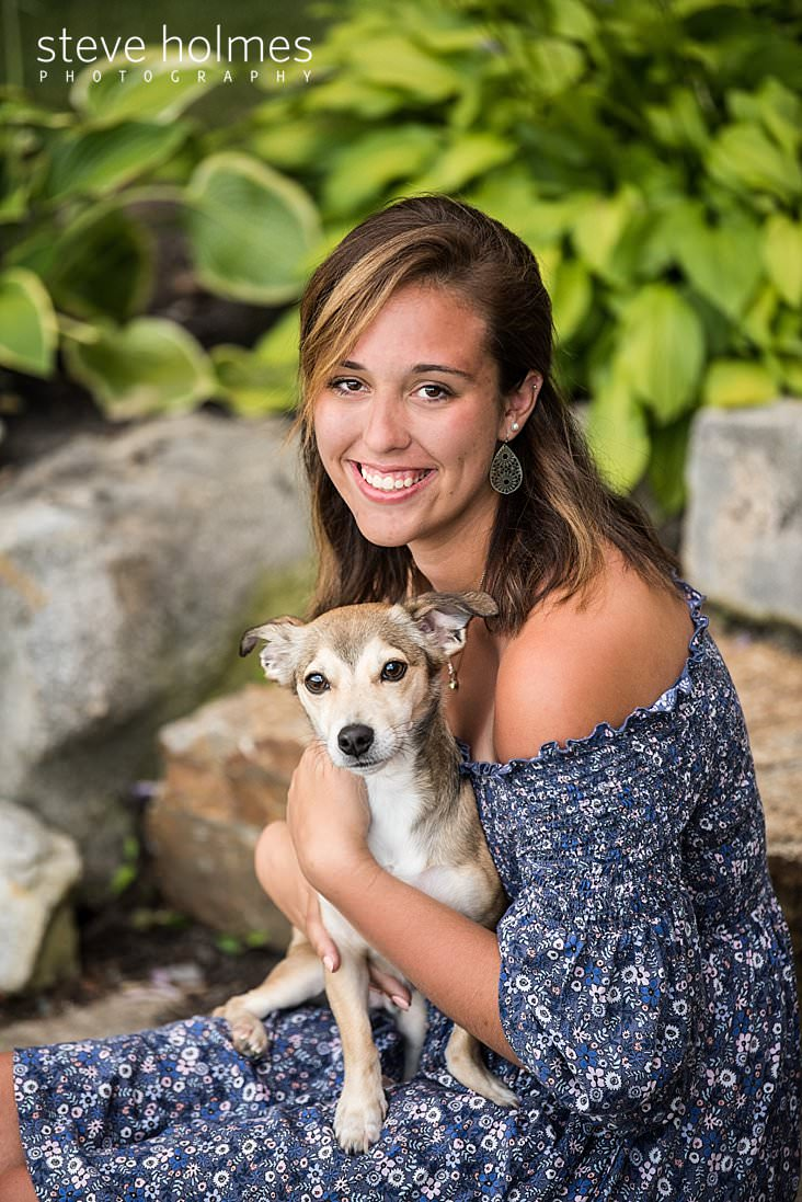 08_Young woman in blue floral dress poses outside with her puppy for senior photo.jpg
