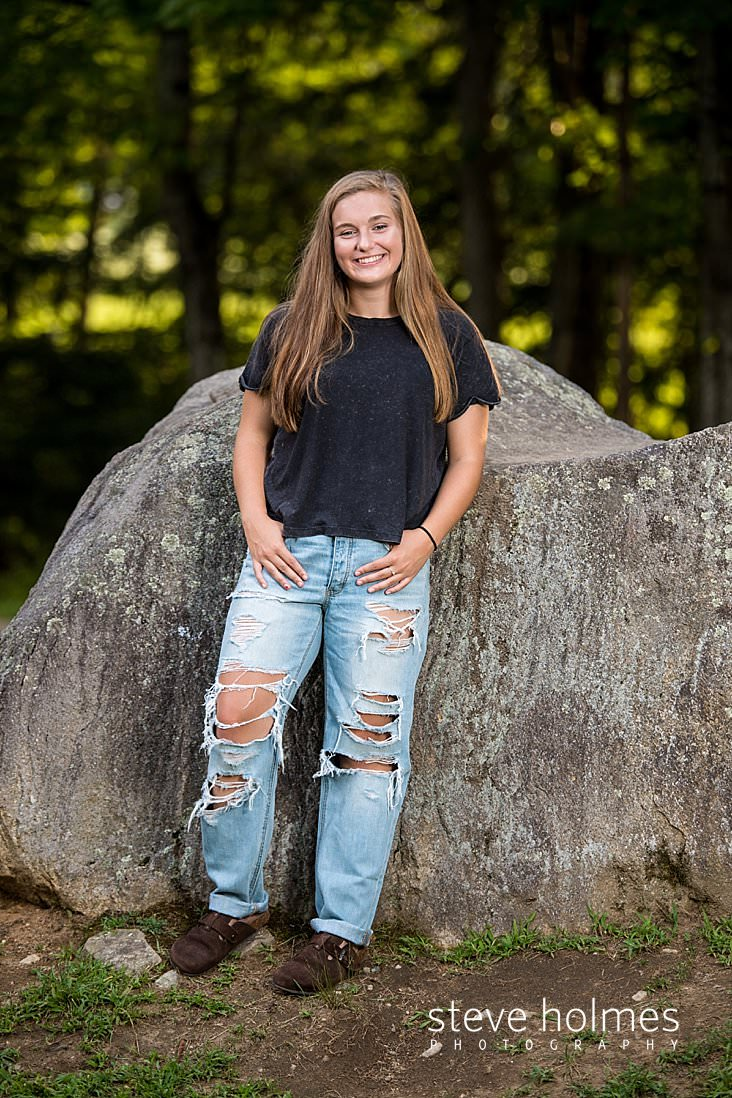 10_Teen girl wearing jeans and a tee shirt leans against a boulder for senior photo.jpg