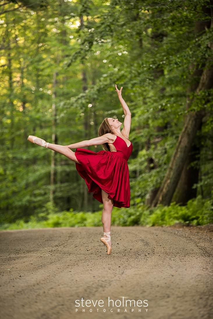 10_Young woman in red dress and ballet shoes dances on country road for senior portrait.jpg