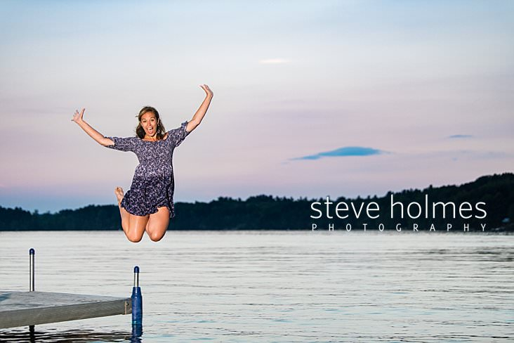 12_Teen girl jumps off dock into water wearing blue floral dress at sunset for senior photo.jpg