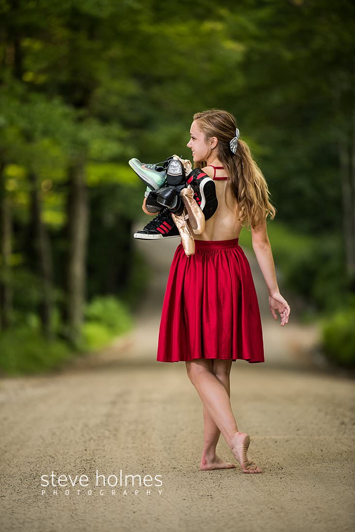 12_Teen girl wearing red dress walks down country road with a collection of shoes thrown over her shoulder.jpg