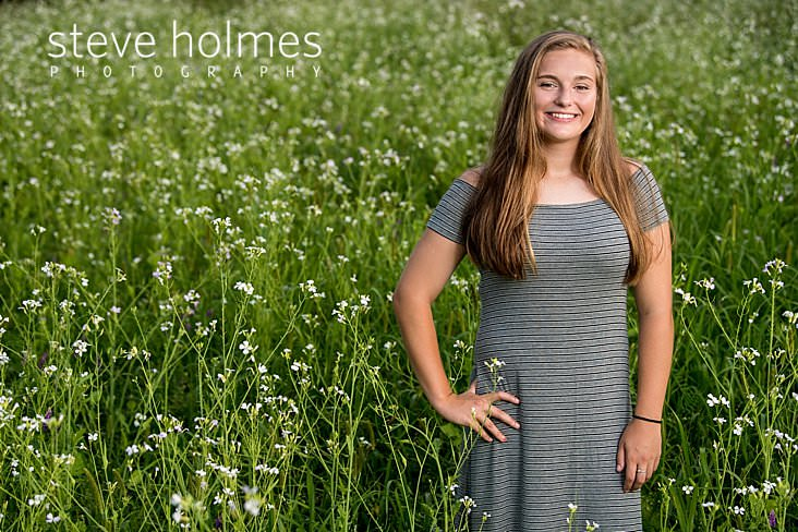 14_Blonde teen wearing grey striped dress stands in field of flowers with her hand on her hip.jpg
