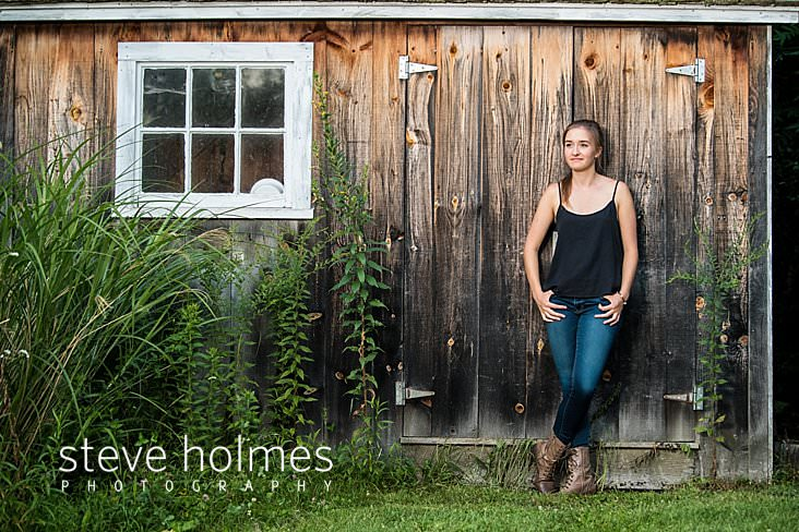15_Teenaged young woman wearing jeans and a black tank top leans against a rustic wooden building for senior portrait.jpg
