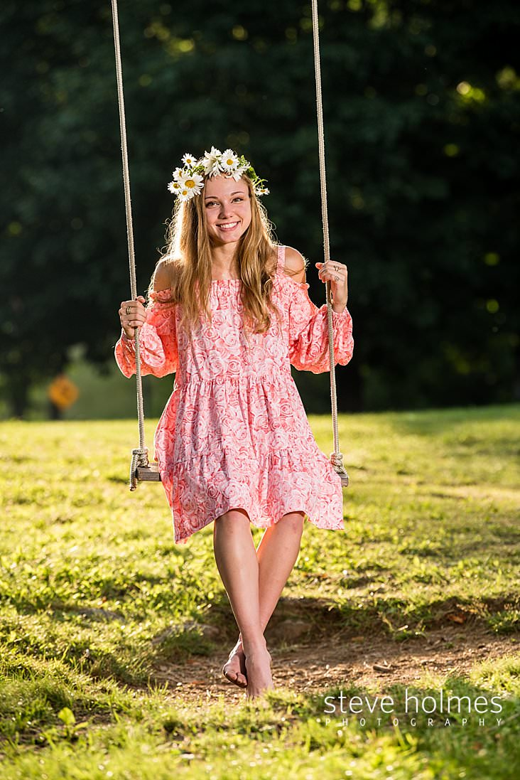 15_Young woman in pink off the shoulder floral dress swings barefoot while wearing daisy crown.jpg