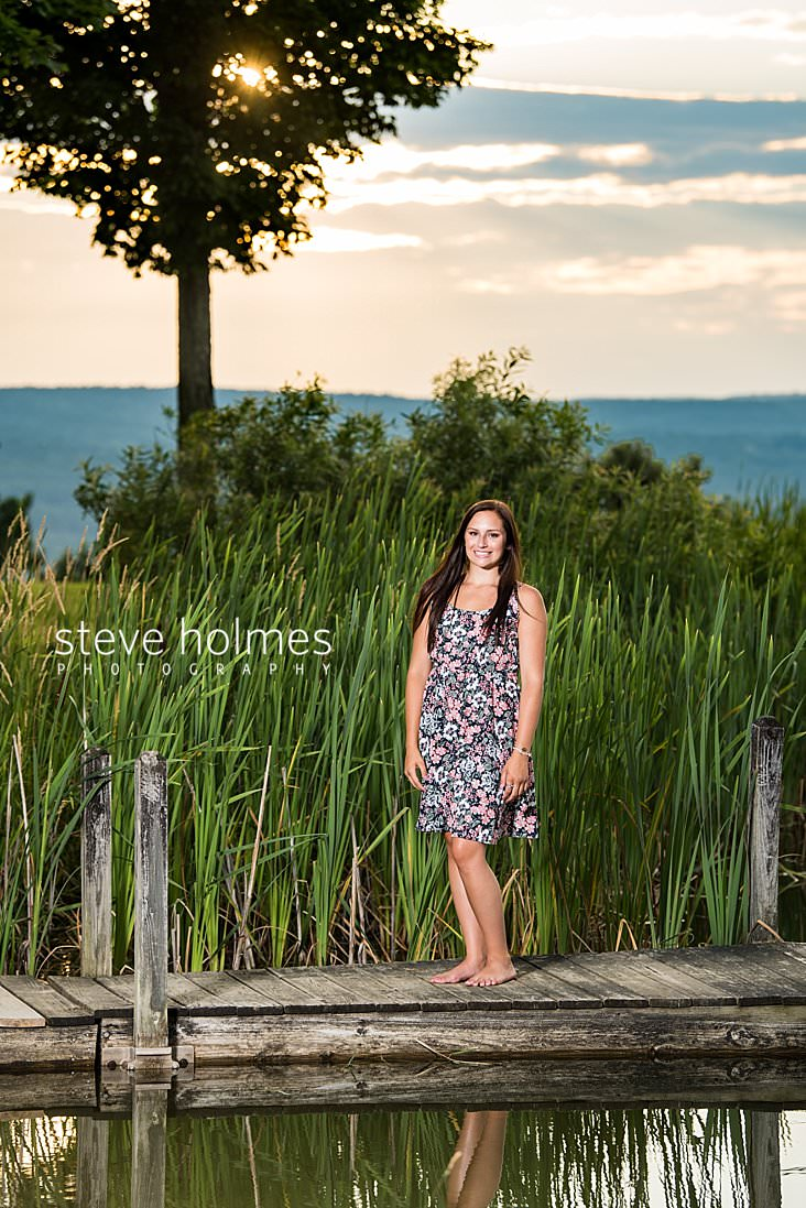 16_Teen girl in floral dress stands on a dock for senior portrait.jpg