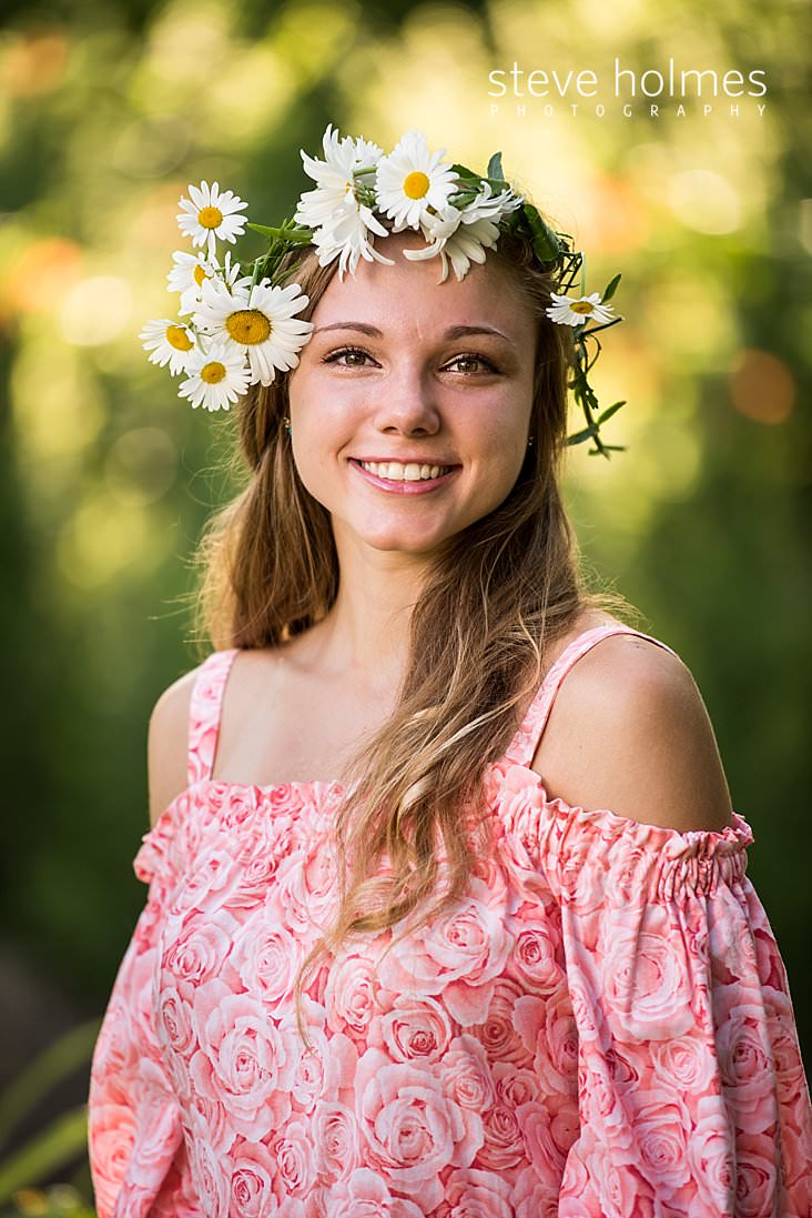 16_Young woman in pink off the shoulder floral dress poses for outdoor senior photo wearing flower crown.jpg
