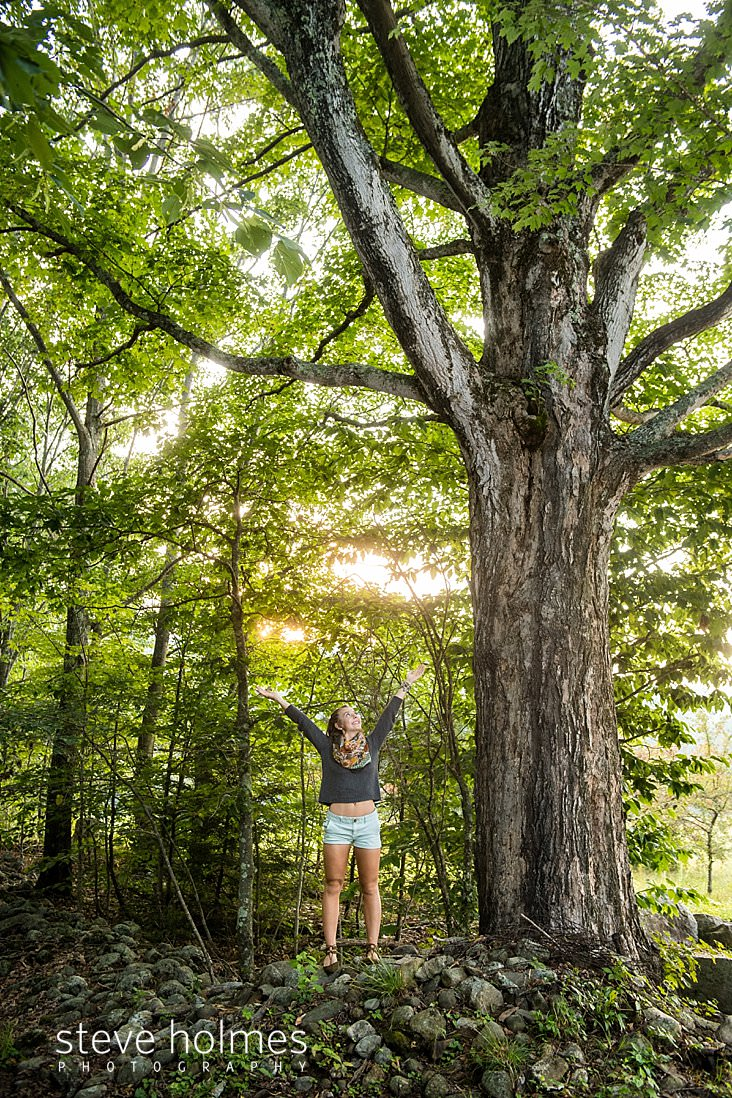 17_Teen girl reaches her arms to the sky under large maple tree in the afternoon sun.jpg