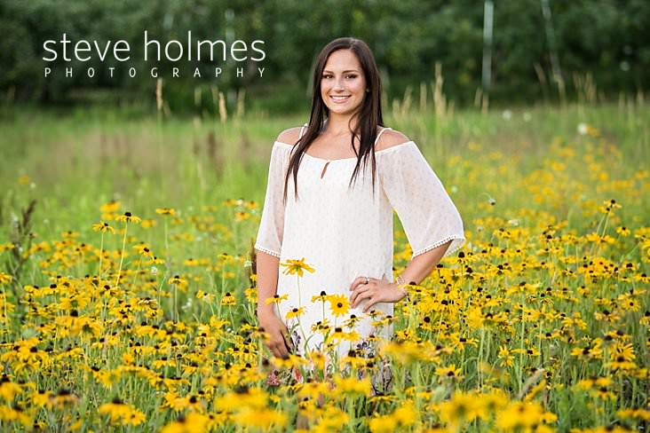 18_Teen girl in white shift dress poses for senior portrait with hand on hip in field of flowers.jpg